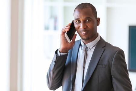 hombres trabajando: Retrato de un joven hombre de negocios del afroamericano que usa un teléfono móvil - los negros Foto de archivo