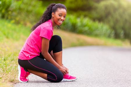 female athlete: African american woman runner tightening shoe lace - Fitness, people and healthy lifestyle