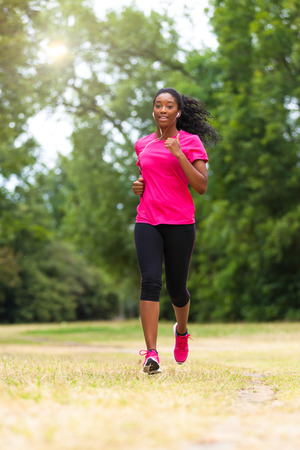 south: African american woman runner jogging outdoors - Fitness, people and healthy lifestyle