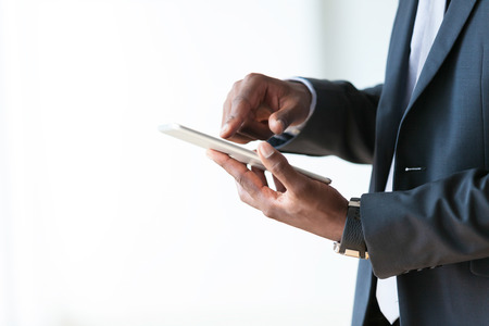 using tablet: African american business man using a tactile tablet over white background - Black people