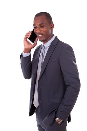 hombres trabajando: Retrato de un joven hombre de negocios estadounidense de hacer una llamada de teléfono móvil - los negros