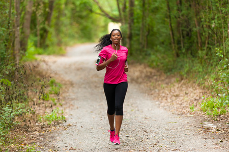 jogging: African american woman runner jogging outdoors - Fitness, people and healthy lifestyle