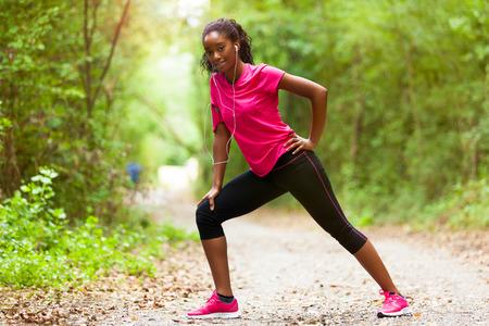 escucha activa: African American mujer corredor de estiramiento - Fitness, la gente y el estilo de vida saludable