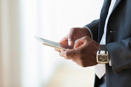personas de pie: African American negocios hombre usando una tableta táctil sobre fondo blanco - los negros