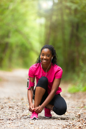lifestyle: African american woman runner tightening shoe lace - Fitness, people and healthy lifestyle