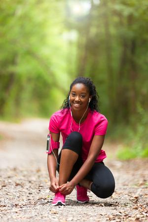 healthy lifestyle: Americana mujer corredor de cordón de zapato endurecimiento de África - fitness, personas y vida sana