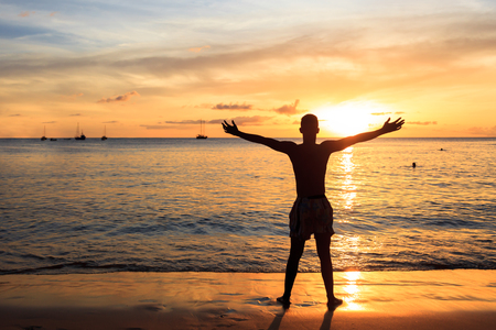 santiago cape verde: African  men raising arms up  at Sunset in Tarrafal beach in Santiago island in Cape Verde - Cabo Verde Stock Photo