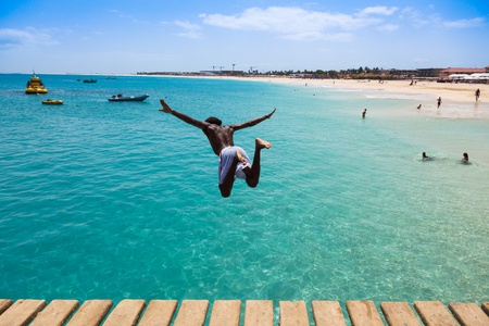 jump: Teenage Cape verdean boy jumping on the turquoise  water of Santa Maria beach in Sal Cape Verde - Cabo Verde