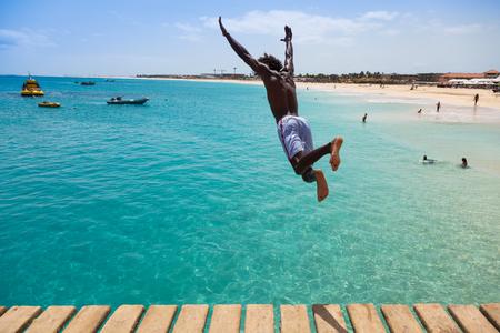 jumping: Teenage boy Cabo Verde saltando sobre el agua turquesa de la playa de Santa María en Sal Cabo Verde - Cabo Verde