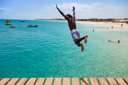 jumping: Teenage Cape verdean boy jumping on the turquoise  water of Santa Maria beach in Sal Cape Verde - Cabo Verde