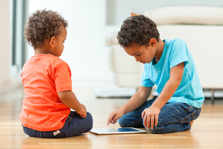 child boy: African american childrens using a tactile tablet