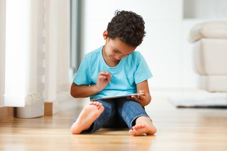 Niño afroamericano usando una tableta táctil Foto de archivo - 45736502