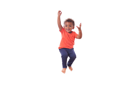 babies playing: Portrait of a cute little African American boy jumping on a trampoline Stock Photo