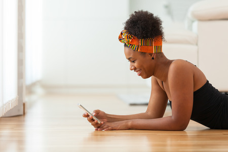 happy african: African American woman sending a text message on a mobile phone - Black people Stock Photo