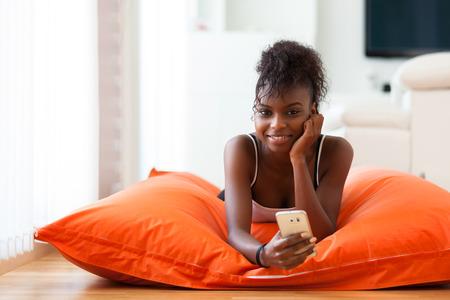 persone nere: African American donna invio di un messaggio di testo su un telefono cellulare - persone di colore