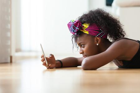 afroamericana: Mujer afroamericana que envía un mensaje de texto en un teléfono móvil - los negros Foto de archivo