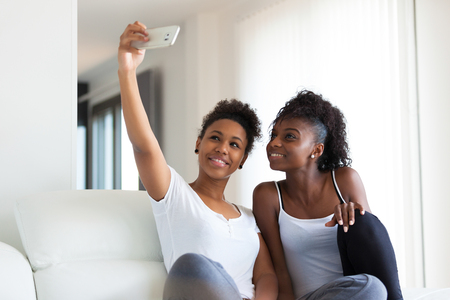 African American teenage girls taking a selfie picture with a smartphone 스톡 콘텐츠