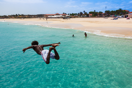 cape: Teenage Cape verdean boy jumping on the turquoise  water of Santa Maria beach in Sal Cape Verde - Cabo Verde