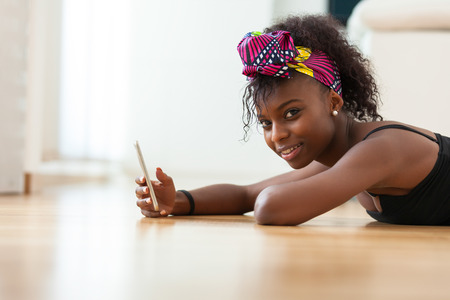 teenagers: African American woman sending a text message on a mobile phone - Black people Stock Photo