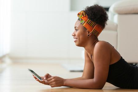 mujeres africanas: Mujer afroamericana que envía un mensaje de texto en un teléfono móvil - los negros Foto de archivo