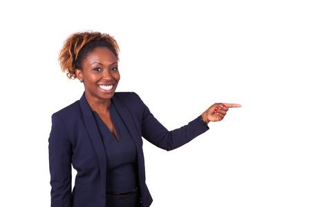 何か、白い背景で隔離を指しているアフリカ系アメリカ人ビジネスの女性