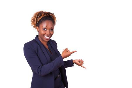 alzando la mano: mujer de negocios afroamericano que señala algo, aislado en fondo blanco Foto de archivo