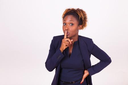 아프리카 계 미국인 비즈니스 여자 그녀의 손가락으로 침묵 제스처를 만드는 스톡 콘텐츠