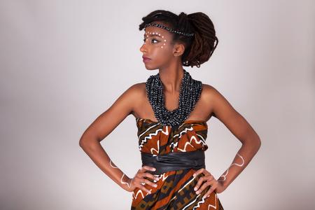 Jonge mooie Afrikaanse vrouw, gekleed in traditionele kleding en sieraden Stockfoto