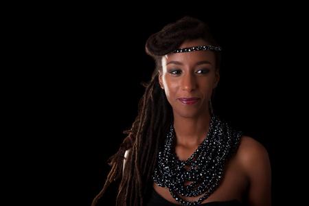 Jonge mooie Afrikaanse vrouw die traditionele juwelen, geïsoleerd op zwarte achtergrond