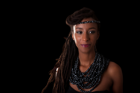 Young beautiful african woman wearing  traditional jewelry, Isolated over black background