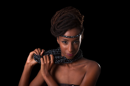 jewelry background: Young beautiful african woman wearing  traditional jewelry, Isolated over black background