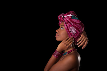 beautiful naked woman: Young beautiful african woman wearing a traditional headscarf, Isolated over black background