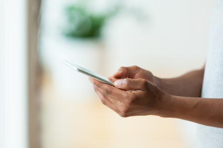 brazilian caribbean: African american person holding a tactile mobile smartphone - Black people Stock Photo