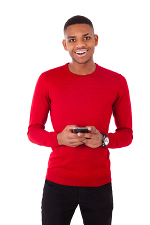 brazilian caribbean: African American young man sending a text message on her smartphone - Black teenager people