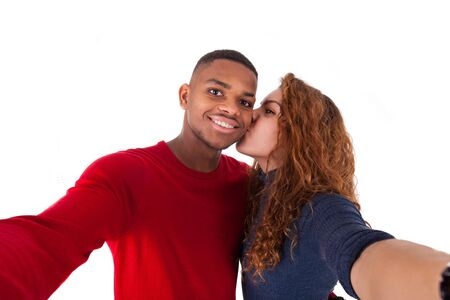happy african: Happy mixed race couple taking a selfie photo over a white background Stock Photo