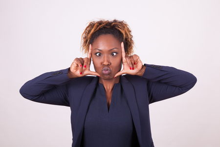 recognition: African American business woman grimacing making frame gesture with her hands, isolated on gray background Stock Photo
