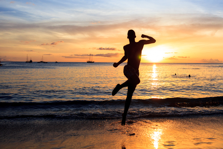 santiago cape verde: African  men jumping  at Sunset in Tarrafal beach in Santiago island in Cape Verde - Cabo Verde