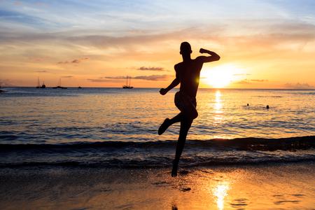 African  men jumping  at Sunset in Tarrafal beach in Santiago island in Cape Verde - Cabo Verde