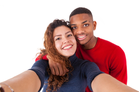 brazilian caribbean: Happy mixed race couple taking a selfie photo over a white background Stock Photo