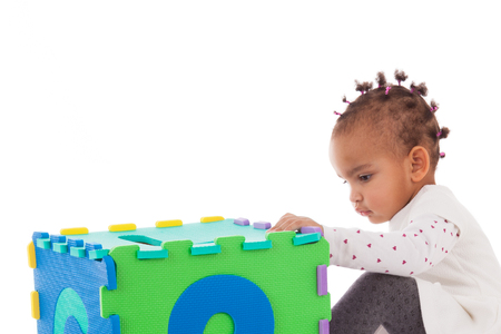 toddler playing: Little African American baby girl playing with construction games isolated on white background Stock Photo