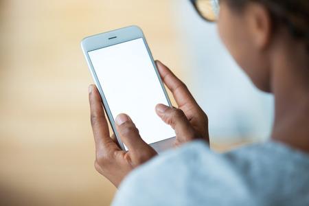 persona del afroamericano que sostiene un teléfono inteligente móvil táctil - los negros Foto de archivo