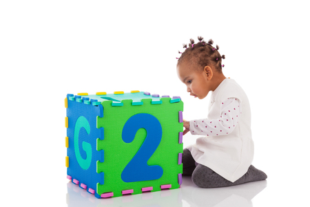 kids toys: Little African American baby girl playing with construction games isolated on white background Stock Photo
