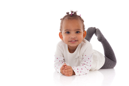 baby isolated: Portrait of little African American little girl lying down on the floor  - Black people Stock Photo