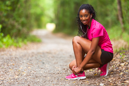 tightening: African american woman runner tightening shoe lace - Fitness, people and healthy lifestyle