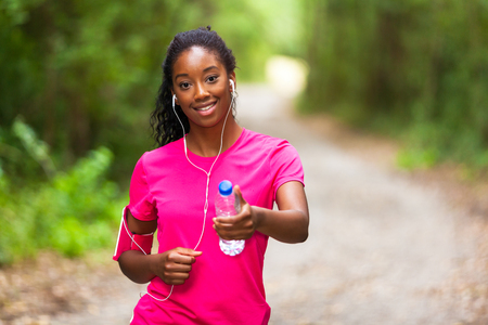 water sports: African american woman jogger holding a water bottle  - Fitness, people and healthy lifestyle