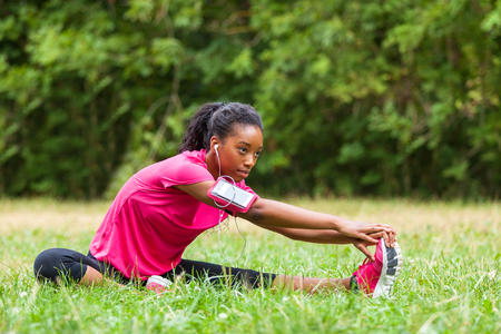 listening music: African american woman jogger stretching  - Fitness, people and healthy lifestyle Stock Photo