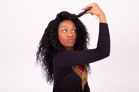 african american woman: Beautiful African American woman touching her curly hairs