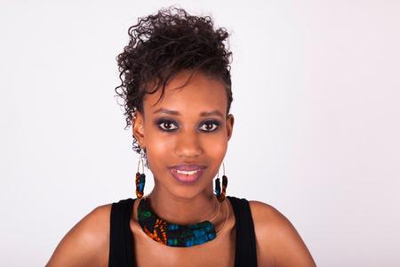 Mooie Afro-Amerikaanse vrouw met krullende haren op een witte achtergrond Stockfoto