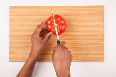 hand lay: African  American womans hand slicing a tomatoe - Flat lay