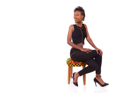 shoe model: Beautiful African American woman sitting on a stool isolated on white background